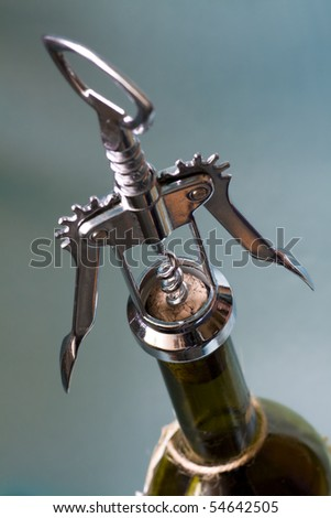 Close shot of a corkscrew opening a bottle of wine. Shallow dof - stock photo