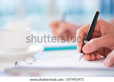Close-shot of a human hand signing a business contract on the foreground - stock photo