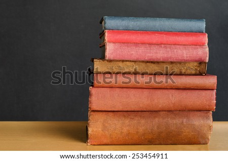 Close shot of a pile of old, shabby, well used text books stacked in a pile on a desk in front of a black chalkboard.  Copy space on left side. - stock photo