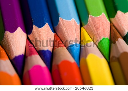 Close shot of a row of colored pencils against a yellow background.