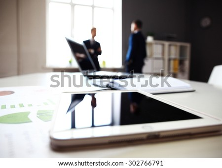 Close-shot of a tablet computer with businessmen handshaking on background - stock photo