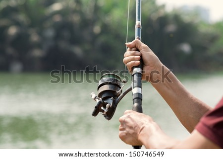 Close-shot of human hands holding a fishing-rod on the foreground - stock photo