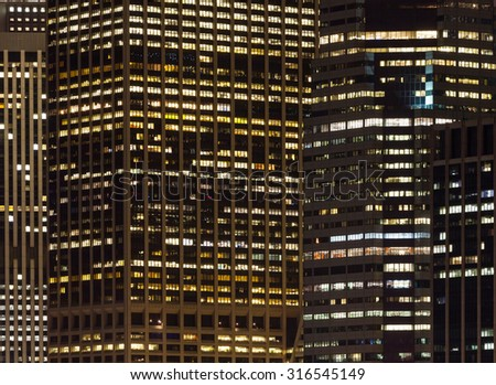 Close shot of skyscrapers with lights on in the offices by night, Manhattan, New York. - stock photo