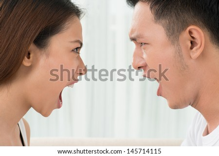 Close-shot of young people's faces shouting during the quarrel  - stock photo