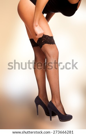 Close side shot of female legs and torso bended, h?nds pooling up black mesh stockings. Image isolated with work path, vertical.