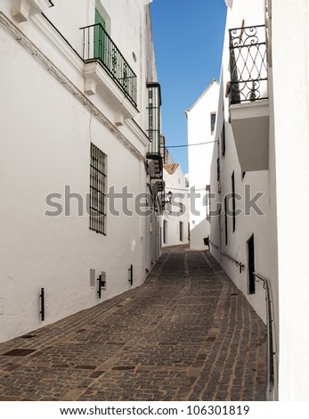 Close street decorated with white houses and bars in their windows. It is a narrow, sloping street. It is Situated in a village in Spain - stock photo