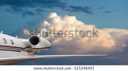 Close tail side view of a private jet flying - stock photo