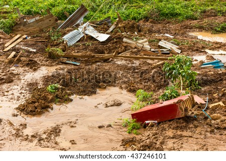 Close to the river, soil erosion, land slides which have a red wooden house ruins and debris. - stock photo