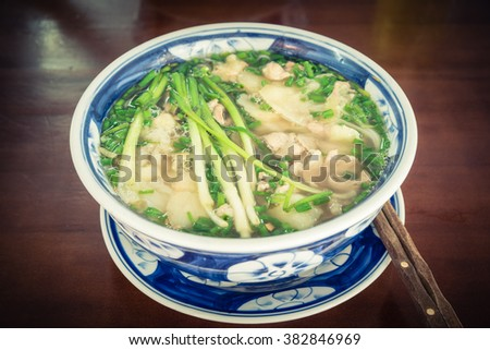 Close-up a bowl of fresh Vietnamese beef rice noodle soup (Pho Bo) served with sliced rare beef, broth, onions, scallions, cilantro and few herbs on wooden table with chopsticks.It popular street food - stock photo