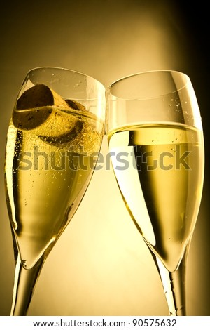 close up a pair of champagne flutes with bottle cap against a golden background - stock photo