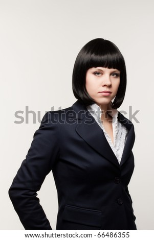 Close up a portrait of the beautiful young woman in a business suit on a light background - stock photo