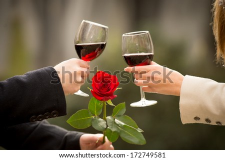 close up a romantic couple drinking wine with a rose in the mans hand on valentines day - stock photo