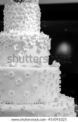 Close up : A white wedding cake. four tiered white wedding cake with black background and bokeh - stock photo
