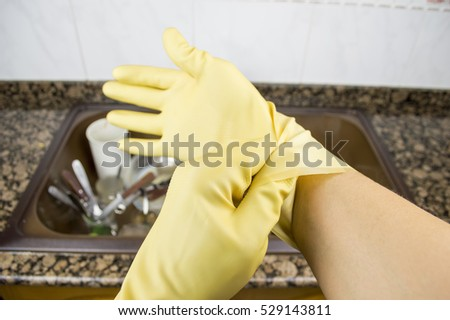 close up a woman putting on the gloves for washing dishes