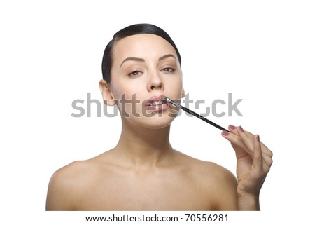 Close up a young beautiful brunette girl with brush on her lip - stock photo