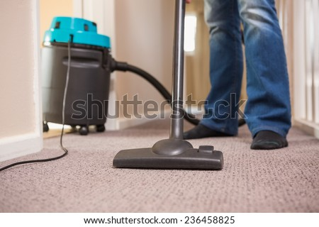 Close up a young man vacuuming at home - stock photo