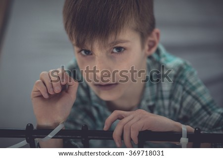 Close up Abused Young Boy Tied on Bed Rail Inside his Room and Looking Straight at the Camera - stock photo