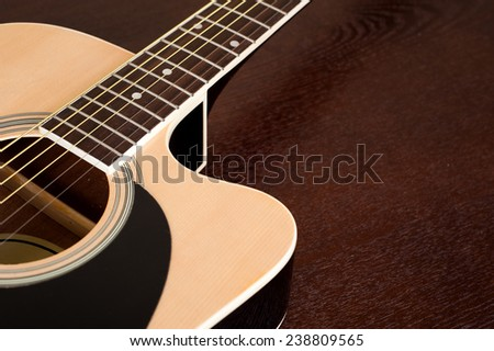 Close-up acoustic guitar on wooden table - stock photo