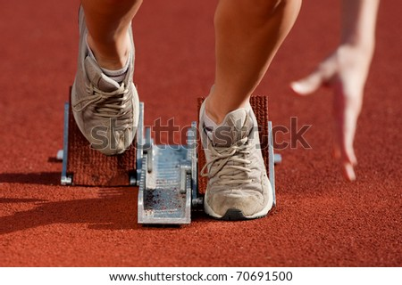 Close up, action packed image of a female athlete leaving the starting blocks for a sprint run on a track - stock photo