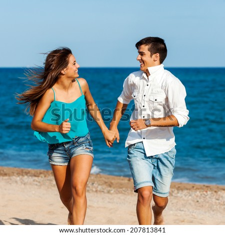 Close up action portrait of Handsome teen couple running together on beach. - stock photo