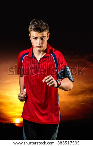 Close up action portrait of teen boy running with at sunset. Boy wearing smart watch and armband with smart phone.