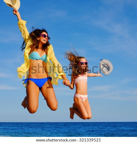 Close up action portrait of young girls on holiday jumping on beach. Two attractive happy women in bikini and sunglasses throwing hats in air. - stock photo