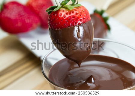 close up action shot of dipping fresh strawberries in dark chocolate at home - stock photo