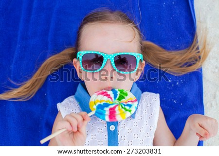 Close up adorable little girl with lollipop on tropical beach - stock photo