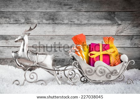 Close up Adorable Silver Reindeer and Santa Sleigh with Presents for Christmas Decoration. Displayed on Man Made Snow with Gray Wooden Wall Background. - stock photo