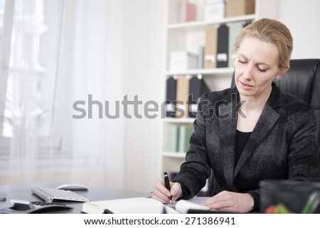 Close up Adult Businesswoman in Black Suit, Sitting at her Desk, Writing on Paper Seriously. - stock photo