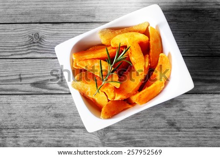 Close up Aerial Shot of Crispy Fried Potatoes in a White Bowl, with Rosemary on Top, Served on Wooden Table. - stock photo