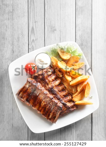 Close up Aerial Shot of Grilled Pork Rib Meat, Crispy Fried Potatoes with Sauce on White Plate. Placed on Gray Wooden Table. - stock photo