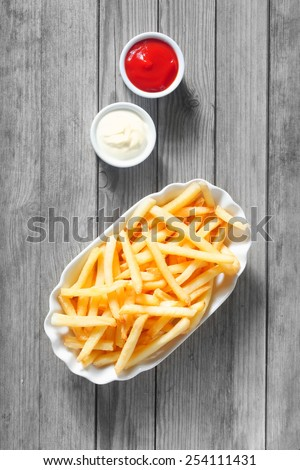 Close up Aerial Shot of Salted French Fries with Dipping Sauces on the Side at the Top of Wooden Table. - stock photo