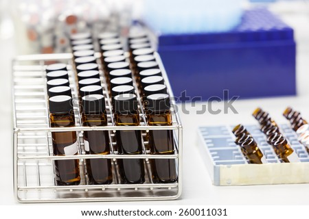 Close up amber color bottle in rack on table, chemistry laboratory - stock photo