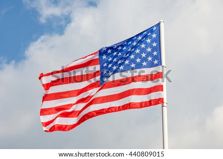 Close-up American flag with flag pole on clear blue sky background. - stock photo