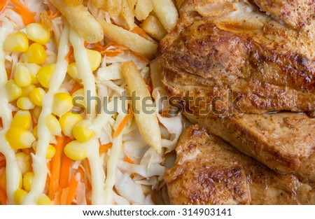 Close up and crop of steak and french fries and vegetable