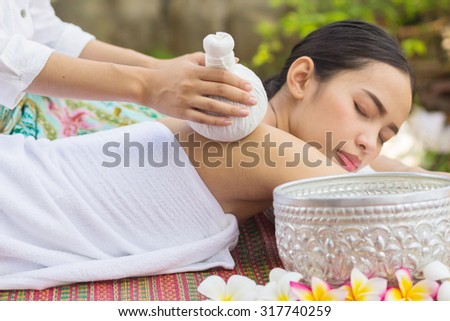 close up and selective focused on hand massaging over young beautiful asian woman lying down:Thai woman in spa treatment :woman relaxing wellness concept.natural outdoors spa treatment concept. - stock photo