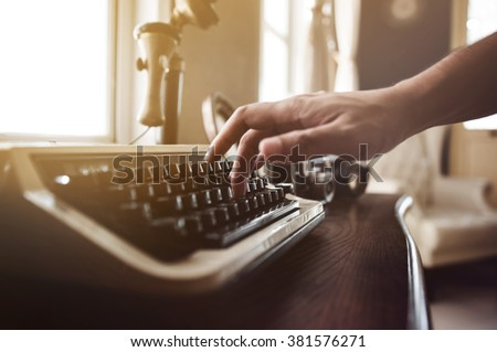 Close up and soft focus of man hand is typing on an old typewriter on wood table with sunlight in the house. Copy space. Vintage - stock photo