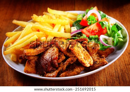 Close up Appetizing Healthy Meal Combination of Cooked Meat, French Fries and Fresh Veggies on Top of Brown Wooden Table. - stock photo