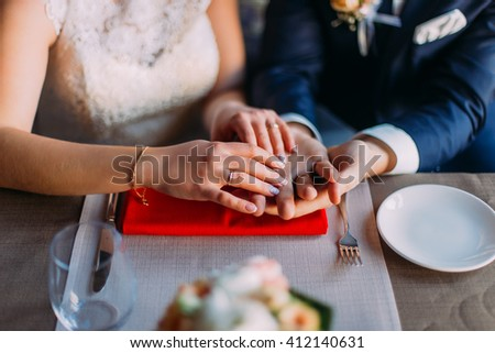 Close up arms of loving couple sitting at the table in cafe - stock photo