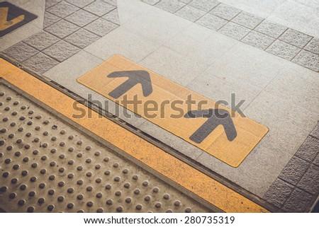 Close up Arrow sign on floor at the sky train station, bangkok, Thailand - stock photo