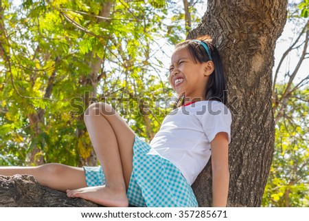Close up asian children climbing trees are afraid of falling trees. - stock photo