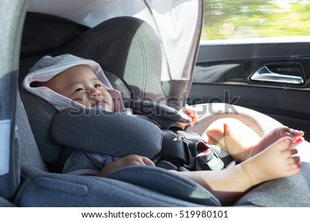 Close Up Asian cute newborn baby sitting in modern car seat. Child new born traveling safety on the road. Safe way to travel fastened seat belts in a vehicle with young kids. Trip with an infant.