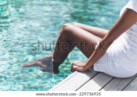 Close up Asian Indian Woman in White Casual Outfit Resting at Poolside with Both Feet on Clear Water - stock photo