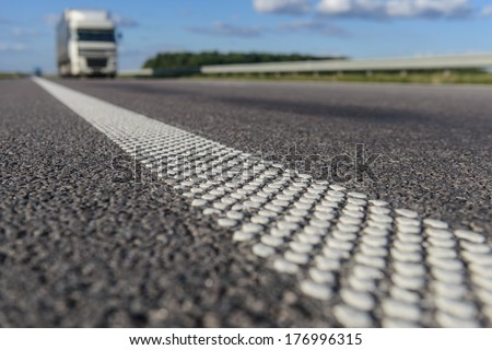 close-up asphalt with dotted white stripe. White truck on the horizon - stock photo
