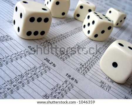 Close-up at short DOF of a number of dice lying on financial newsparer figures