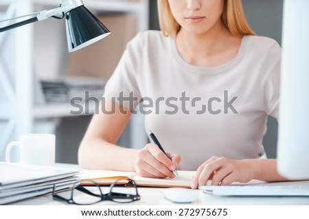 Close-up at work. Close-up of beautiful young woman holding hand on chin and looking at camera while sitting at her working place in office - stock photo
