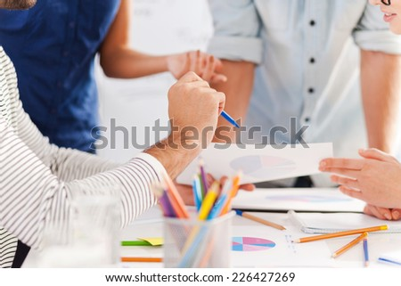Close-up at work. Close-up of business people in smart casual wear discussing something while leaning at the table - stock photo
