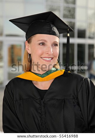 close-up attractive blond woman in graduation cap and gown on campus