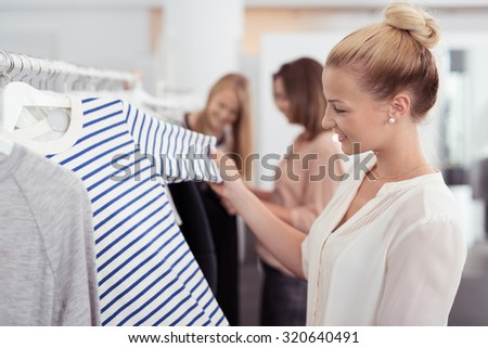 Close up Attractive Blond Woman Looking for Casual Striped Shirt inside a Clothing Store. - stock photo